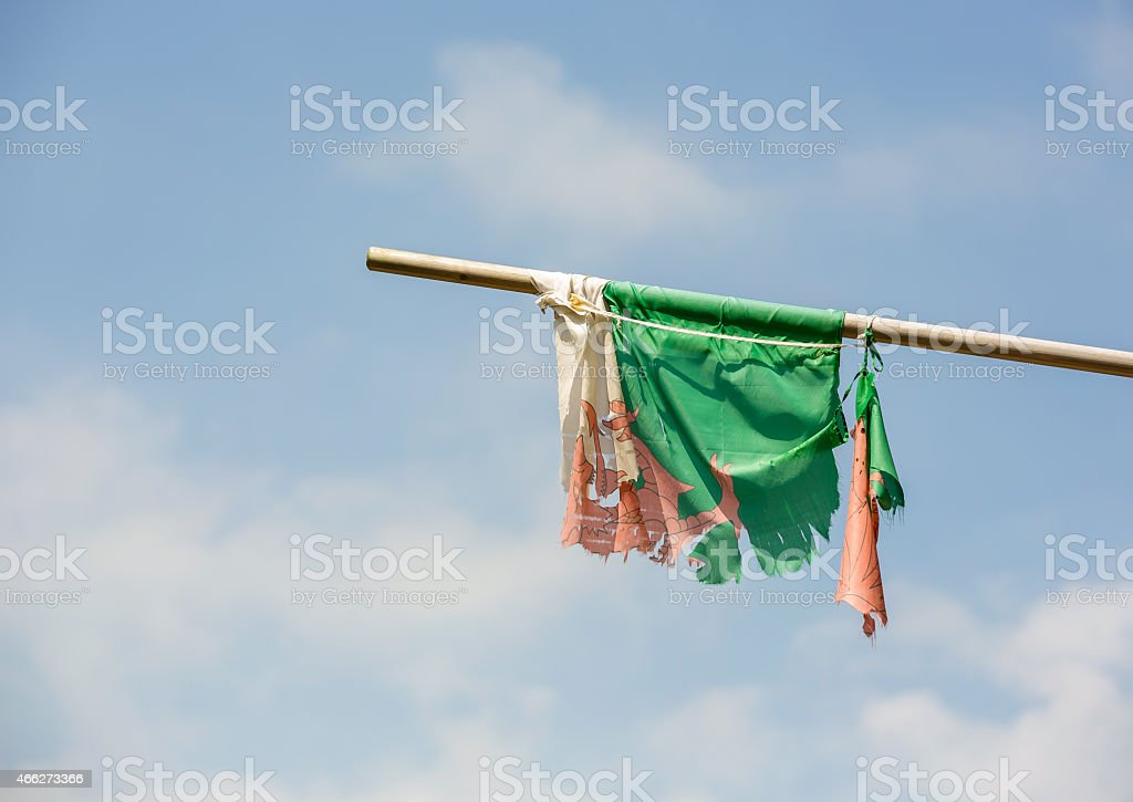 Welsh flag mounted on a horizontal flagpole looking very worn royalty-free stock photo
