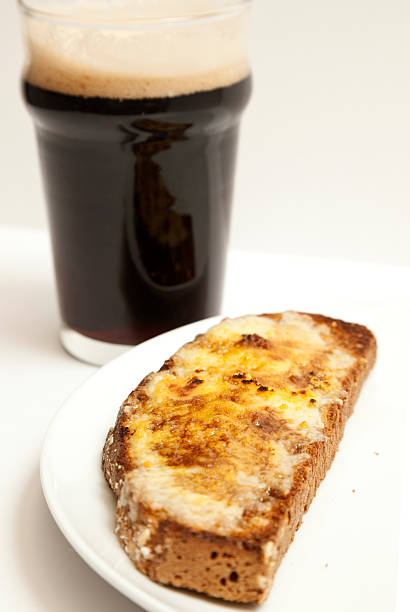 Welsh Rarebit and Stout A slice of Welsh rarebit (cheese on toast) with a glass of stout.  Shallow depth of field.See similar images in my Food & Drink Lightbox welsh culture stock pictures, royalty-free photos & images
