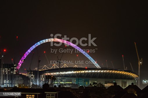 Stadium arch in rainbow colours at night, London, UK.
