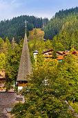 Wengen, Switzerland town view and church tower in alpine village in Swiss Alps, autumn mountains around, popular resort in Bernese Oberland