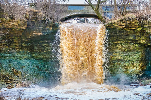 wequiock falls near, green bay wisconsin, raging with muddy waters - green bay wisconsin stock photos and pictures