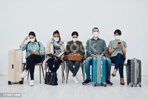 Shot of a group of young people wearing masks while waiting together in an airport lounge