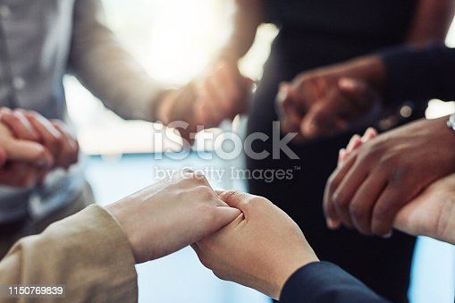Cropped shot of a group of businesspeople standing together and holding hands in a modern office