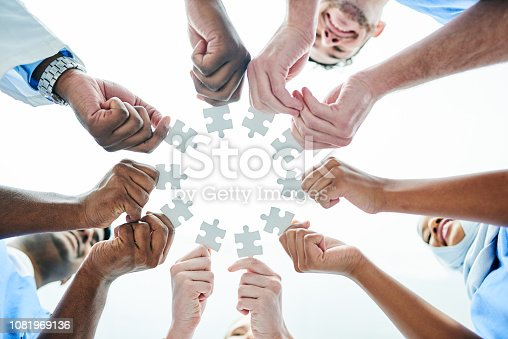 Low angle shot of a team of doctors matching puzzle pieces together in a hospital