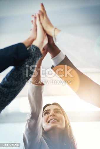 Cropped shot of  group of businesspeople gathering for a high five