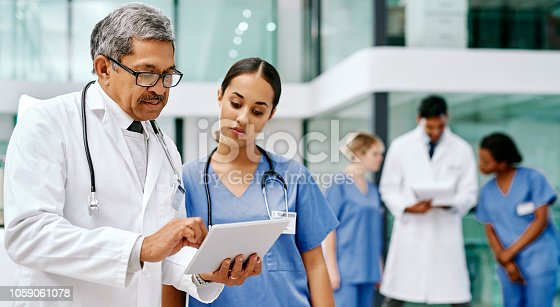 Shot of two medical practitioners using a digital tablet together in a hospital