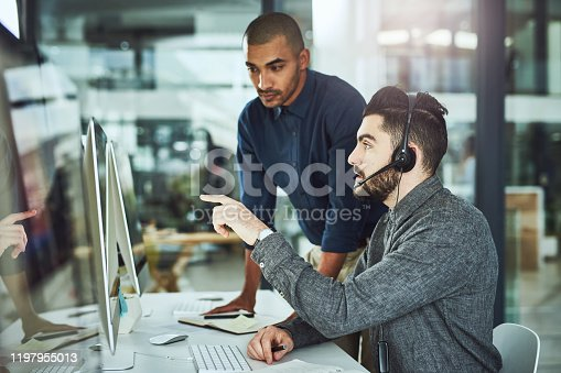Shot of a young businessman assisting a colleague in a call centre