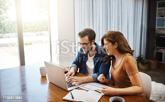 Shot of a young couple doing some online shopping on a laptop together over the weekend at home