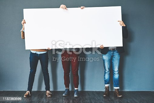Studio shot of businesspeople holding up a blank sign against a grey background