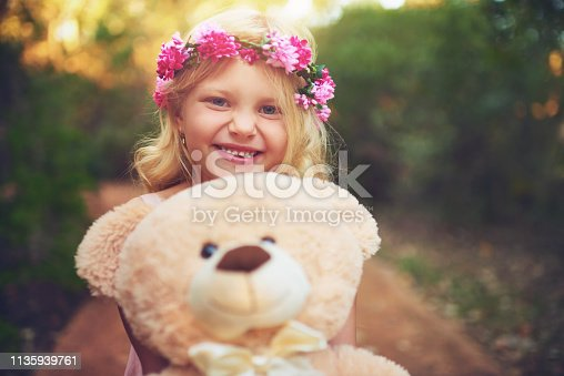 Shot of a happy little girl holding a teddy bear and looking at the camera while standing in the middle of a dirt road