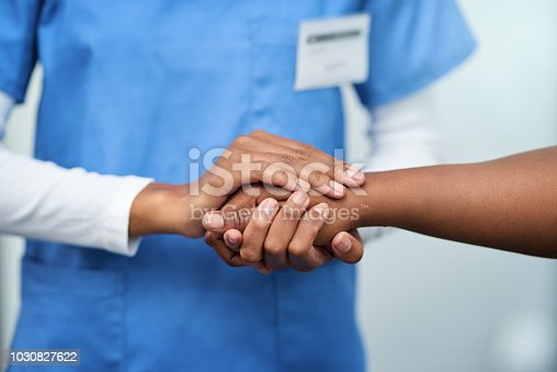 Closeup shot of a nurse holding a patient's hand in comfort