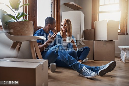 Shot of a couple taking a break from unpacking in their new home