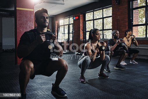 Shot of young people working out in the gym
