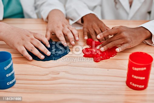 Cropped shot of two unrecognizable school pupils playing and experimenting with slime in science class at school