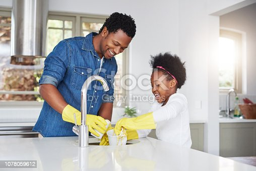Shot of a little girl and her father enjoying their chores at home