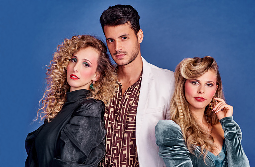Shot of three young people posing together in 80s clothing against a blue background