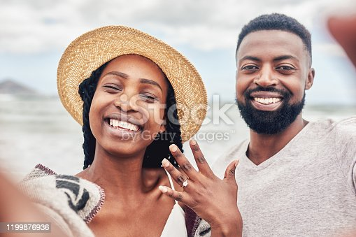 POV shot of a young couple taking selfies on the beach after their engagement