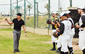 Full length shot of a young baseball coach talking to his team during a training session on the pitch outdoors