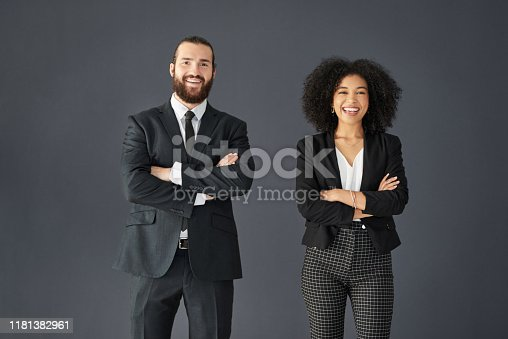 Studio portrait of two young corporate businesspeople posing together with their arms folded against a grey background