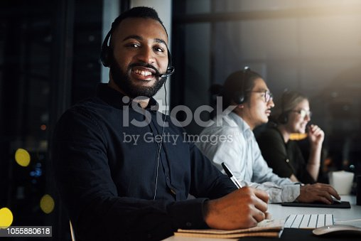 Cropped portrait of a male IT support staff member working the late shift with his team in their office