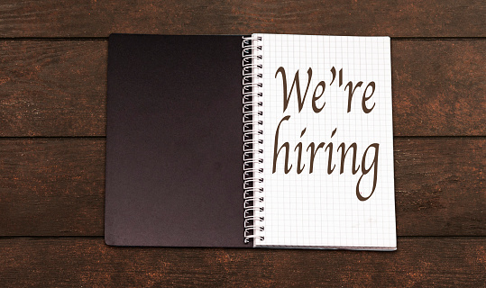 istock we're hiring concept on wood table 1203597485