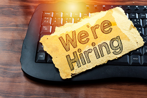 istock we're hiring text in old paper above black keyboard 1135168078