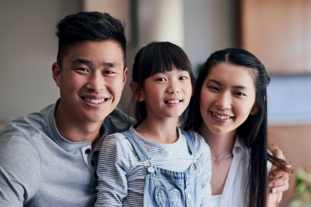 We're just a happy family Portrait of a happy family bonding together at home korean ethnicity stock pictures, royalty-free photos & images