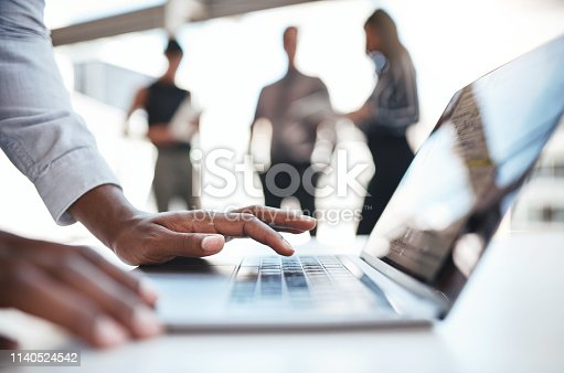 Cropped shot of an unrecognizable businessman using a laptop while his colleagues stand in the background