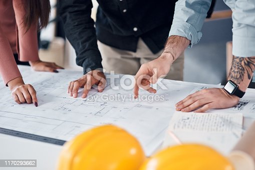 Shot of three unrecognizable architects going over blueprints and building plans together in their office