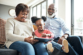 Shot of a little girl using a digital tablet with her grandparents at home