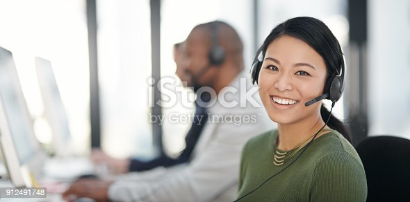 Portrait of a call centre agent working alongside her colleagues in an office