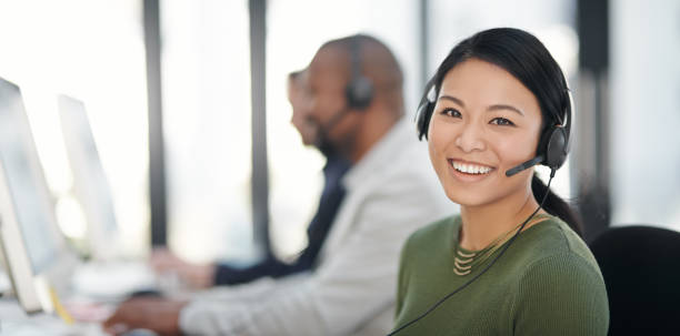 We're more than happy to help Portrait of a call centre agent working alongside her colleagues in an office call centre photos stock pictures, royalty-free photos & images