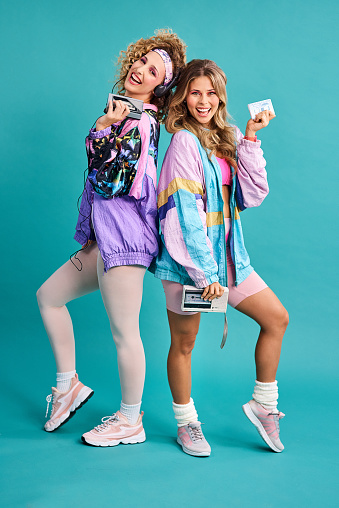 Studio shot of two beautiful young women styled in 80s clothing