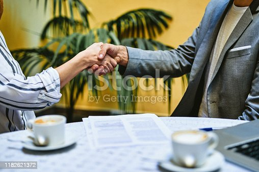 Cropped shot of two unrecognizable businesspeople shaking hands after having a meeting together inside a coffeeshop