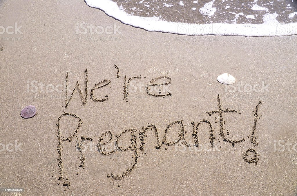 We're Pregnant! Written in beach sand stock photo