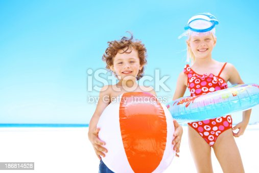 Sweet young siblings holding inflatable toys while standing on the beach - copyspace