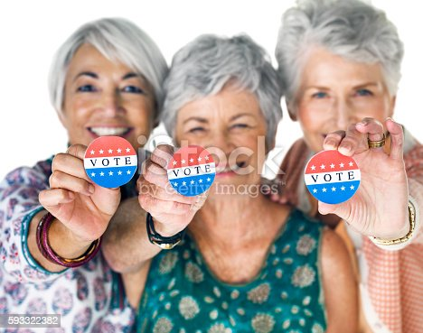 Studio portrait of a group of senior women holding up election buttons against a white background