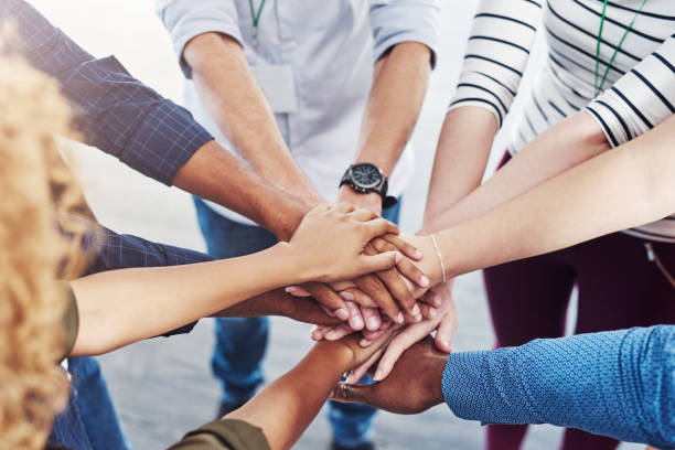 We're stronger when we unite together Closeup shot of a group of people joining their hands together in a huddle hand stock pictures, royalty-free photos & images
