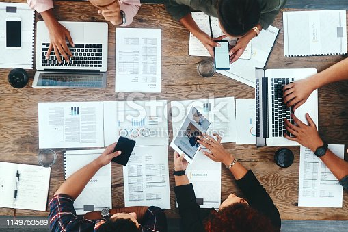 High angle shot of a group of young businesspeople using their digital devices during a meeting at work