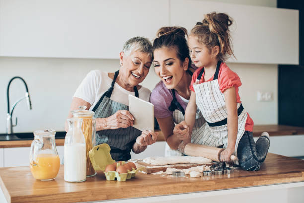 We're trying anew recipe Different generations of women with digital tablet preparing cookies together stay at home order stock pictures, royalty-free photos & images