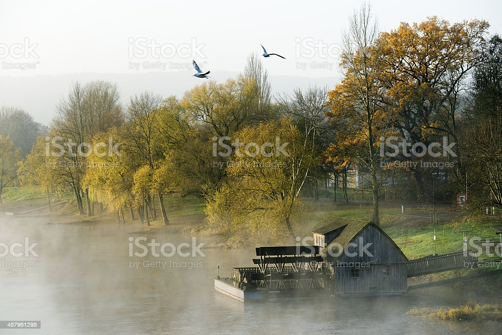 Weser river with historical watermill in autumn stock photo