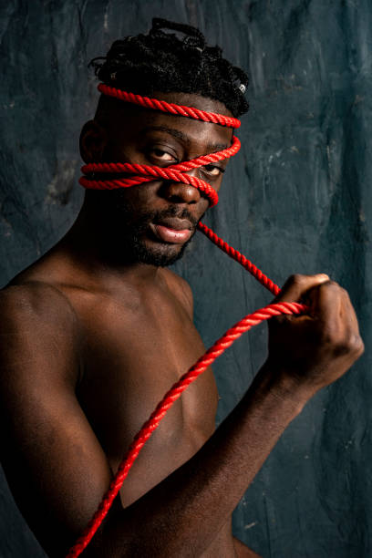 West African Man Experiments With Decoration Of The Body Using Red Rope Stock Photo Download Image Now Istock