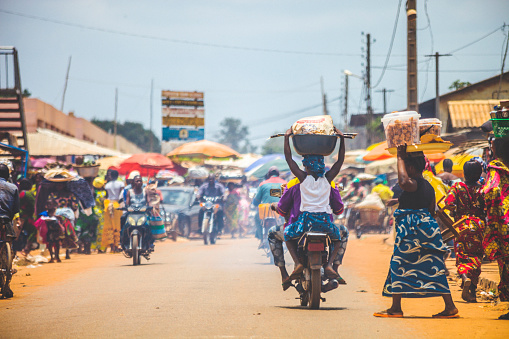 Bohicon, Benin - September 8, 2012: People crossing the street in busiest market junction in town, lot of motorbikes in background.
