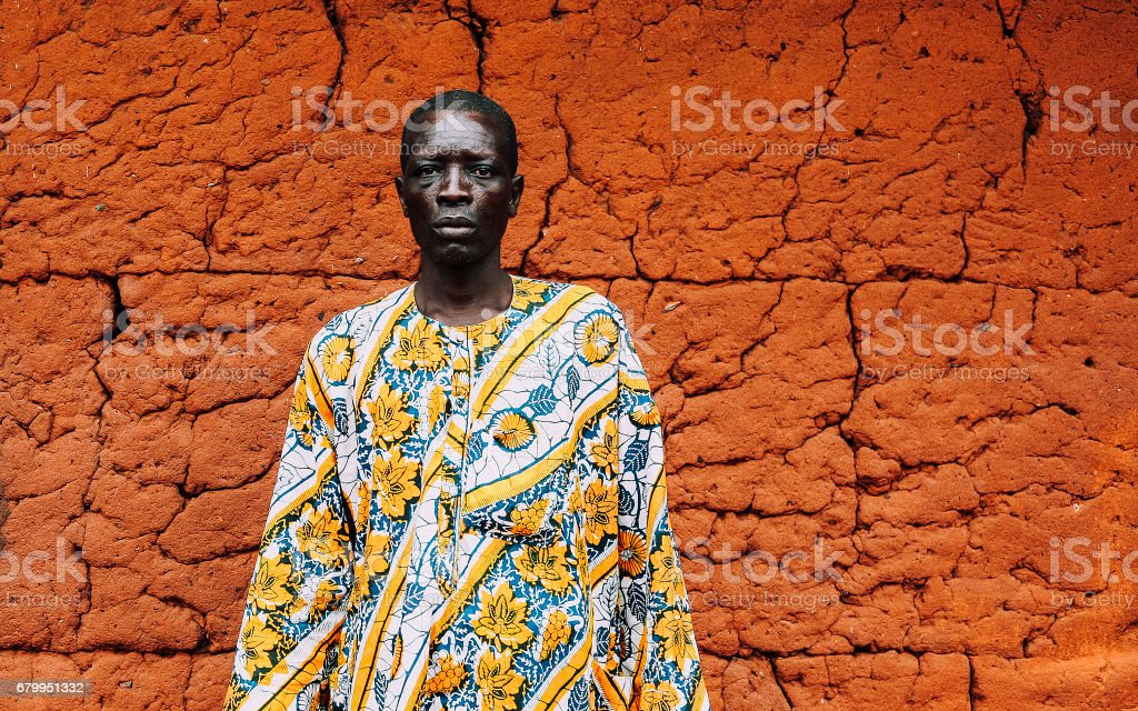West African senior in front of mud hut. stock photo