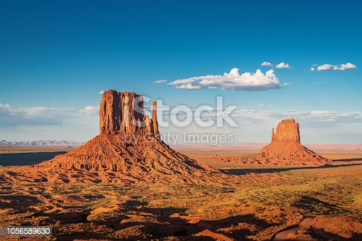 Scenic view to the famous West and East Mittens Buttes in warm late afternoon light under beautiful summer sky. Monument Valley, Arizona, USA.