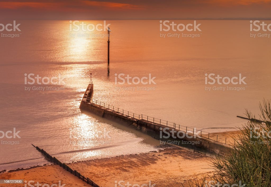 West cliff Ramsgate, uk beach and water breaker walkway late afternoon in winter as the sun is starting to set,making the sea shimmer and the light turn golden stock photo