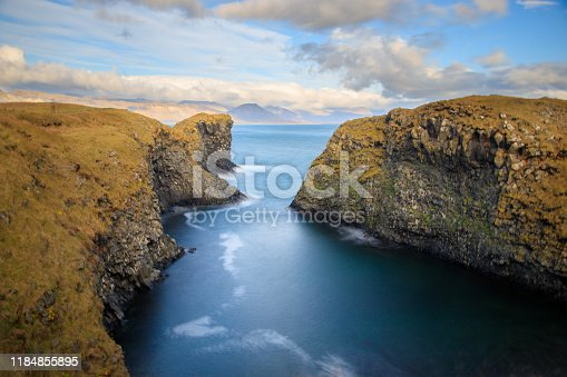 istock West coast sea cliffs of Snaefellsnes Peninsula on Iceland in long exposure photo. Pure blue water with high cliffs above sea. Beautiful colourful scenic view of basalt rock reef. 1184855895