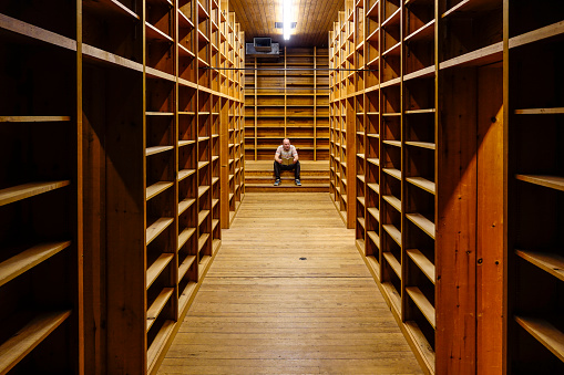 West Cornwall, Ct, USA A man stands in an old and empty antiquarian bookstore reading one book.