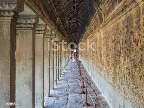 Siem Reap, Cambodia - February 8, 2016: Tourists admire the bas-reliefs in the West gallery of Angkor Wat