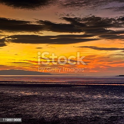 View of the sun setting over West Kirby beach, Wirral.